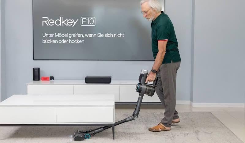 Mann saugt mit RedKey F10 unter einem Tisch